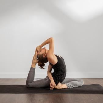 Mulher saudável fazendo ioga em casa