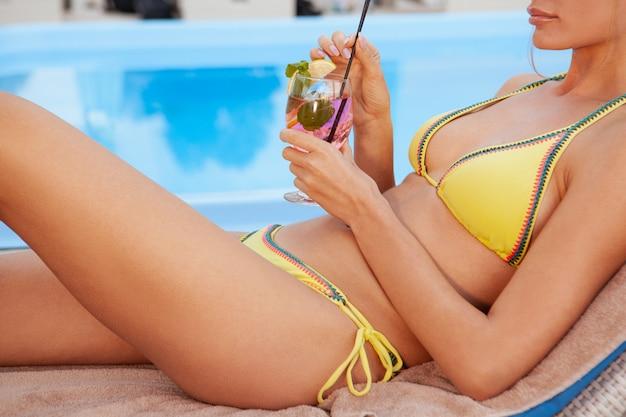 Mulher saudável feliz relaxante ao lado da piscina do hotel