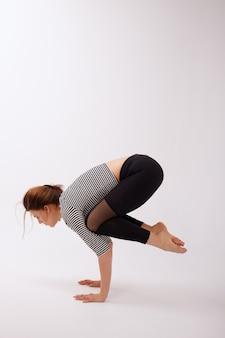 Mulher saudável na caneleira preta dos esportes que faz o asana de bakasana em um fundo isolado branco. dia da ioga