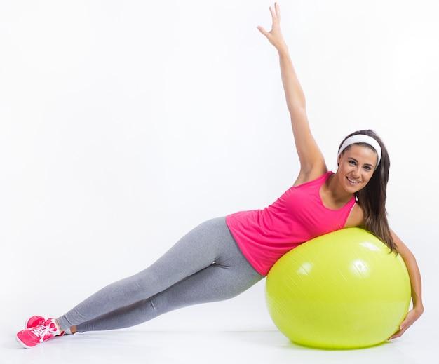 Mulher saudável nova bonita que faz o exercício em casa.