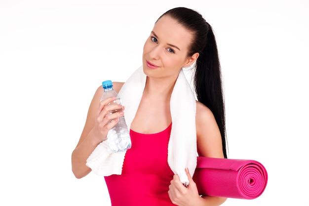 Mulher saudável segurando uma garrafa de água e uma esteira para exercícios