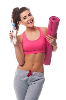 Mulher saudável segurando uma garrafa de água mineral e uma esteira para exercícios