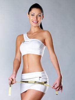 Mulher saudável sorridente depois de fazer dieta mede o quadril. estilo de vida saudável.