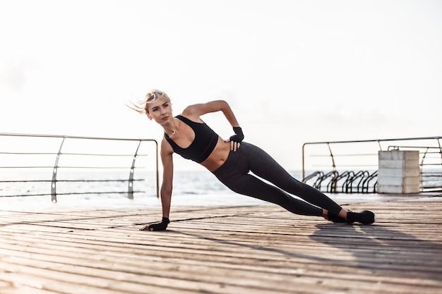 Mulher saudável treinando no calçadão à beira-mar. jovem mulher esportiva em roupas esportivas fazendo exercícios de prancha lateral na praia