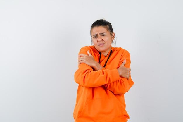 Mulher se abraçando ou sentindo frio em um capuz laranja e parecendo desamparada