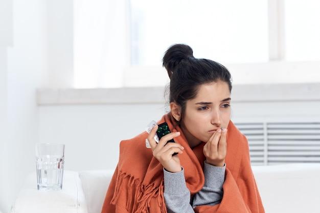 Mulher se abrigando com manta em casa medicação tratamento descontente