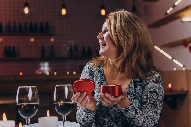 Mulher se alegra abrindo uma caixa com um presente para o dia dos namorados em um restaurante