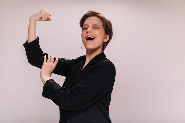 Mulher se alegra com seu poder e demonstra seus bíceps. senhora encantadora de jaqueta preta sorri e mostra músculos em um fundo isolado