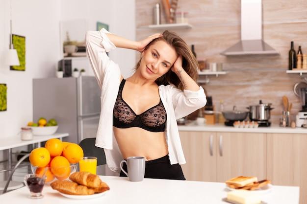 Mulher se alongando depois de tecer usando cueca sexy na cozinha de casa.