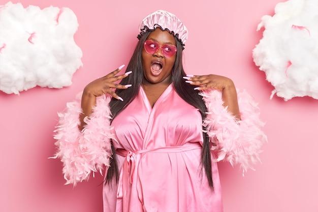 Mulher se ama levanta as mãos tem manicure rosa usa chapéu de banho, óculos de sol em formato de coração e roupão posa dentro de casa