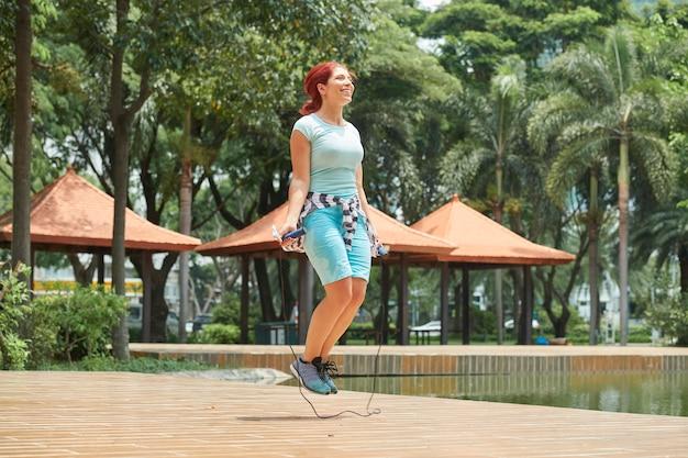 Mulher se aquecendo com pular corda
