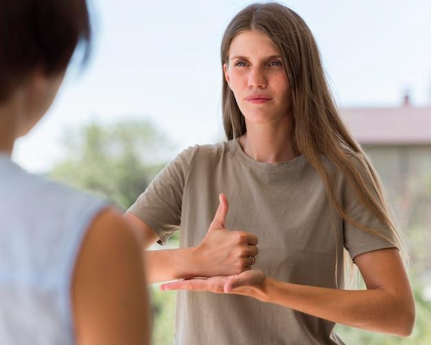 Mulher se comunicando por meio de linguagem de sinais ao ar livre