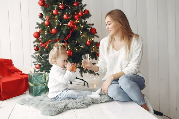 Mulher se diverte se preparando para o natal. mãe de suéter branco brincando com a filha. família está descansando em uma sala festiva.