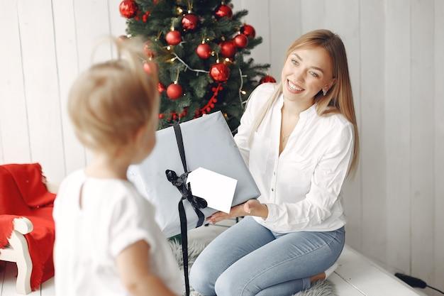 Mulher se diverte se preparando para o natal. mãe em uma camisa branca está brincando com sua filha. família está descansando em uma sala festiva.