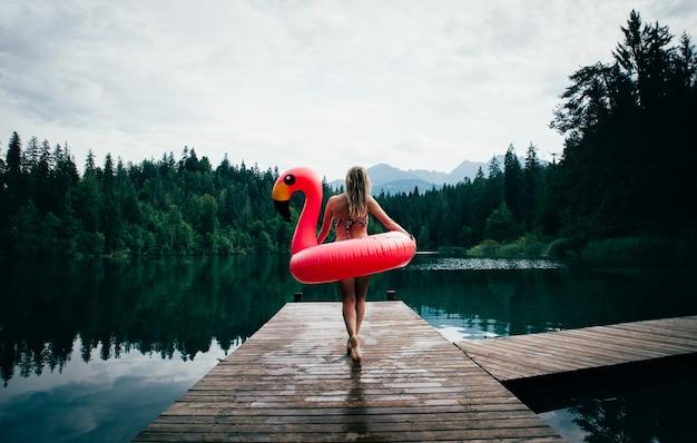 Mulher se divertindo com flamingo no lugar do lago