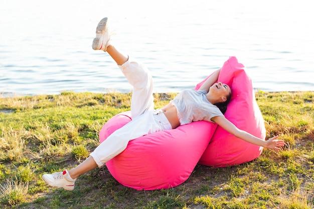 Mulher se divertindo em pufes rosa