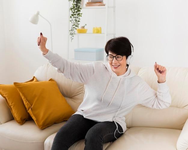 Mulher se divertindo no sofá enquanto ouve música em fones de ouvido