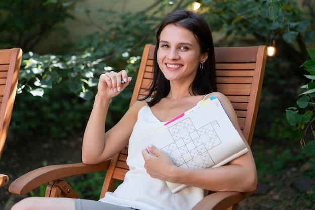 Mulher se divertindo sozinha com um jogo de sudoku no papel