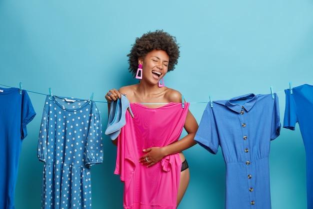 Mulher se esconde atrás do vestido rosa segura sapatos de salto alto, vestidos para ocasiões especiais tem uma expressão alegre isolada na parede azul.