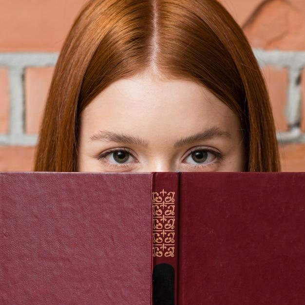 Mulher se escondendo atrás de um livro