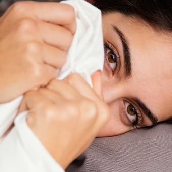 Mulher se escondendo sob os lençóis em casa