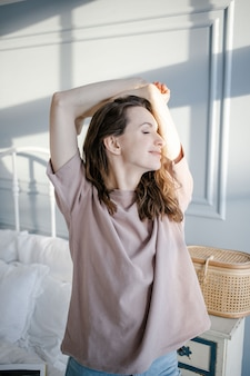 Mulher se espreguiçando depois de uma noite de sono