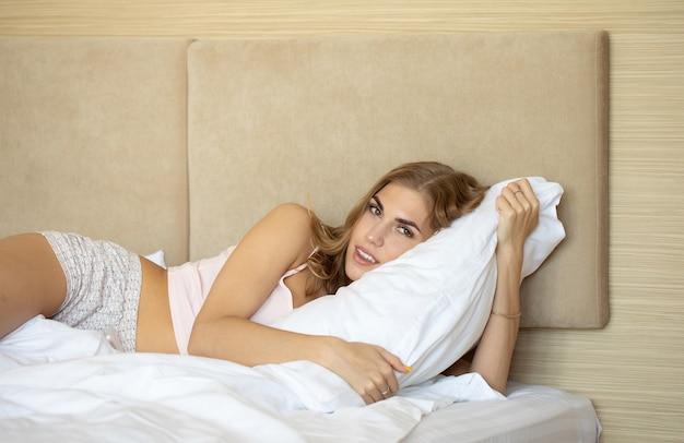 Mulher se espreguiçando na cama depois de acordar.