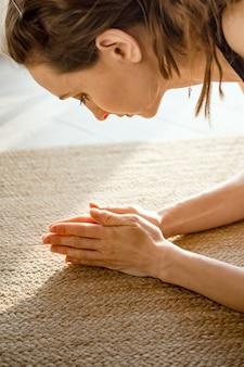 Mulher se esticando para a frente, fazendo uma pose de ioga no tapete