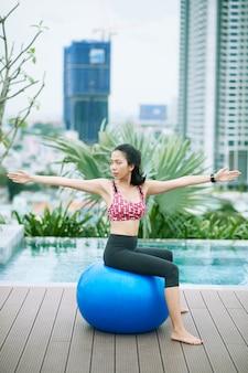 Mulher se exercitando com a bola