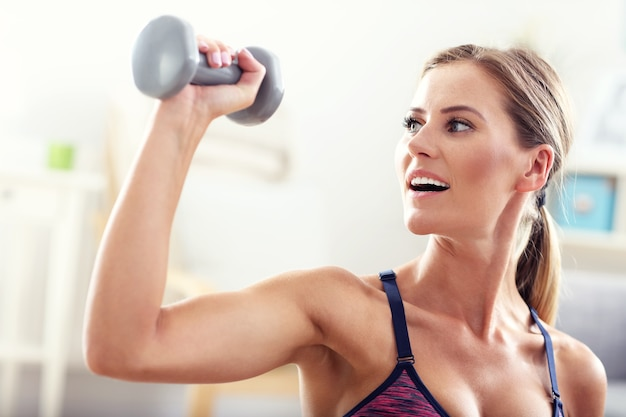 Mulher se exercitando com halteres em casa