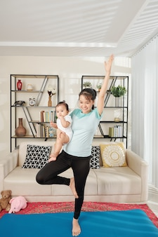 Mulher se exercitando com o bebê nas mãos