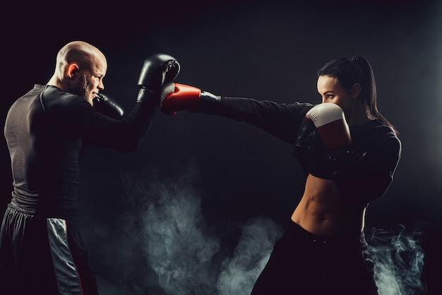 Mulher se exercitando com o treinador em aula de boxe e defesa pessoal, estúdio, fumaça no espaço