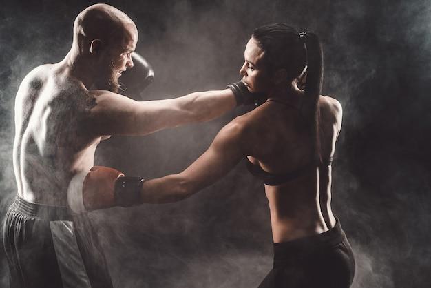 Mulher se exercitando com o treinador na aula de boxe e defesa pessoal