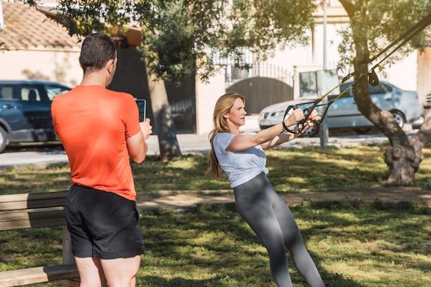 Mulher se exercitando com um trx em um parque com um personal trainer ao lado dela que está tirando uma foto com o celular