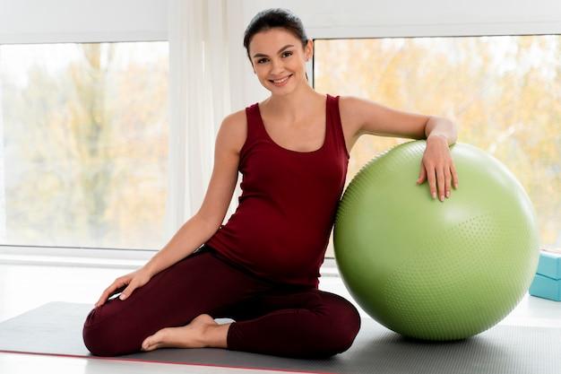 Mulher se exercitando com uma bola de fitness durante a gravidez