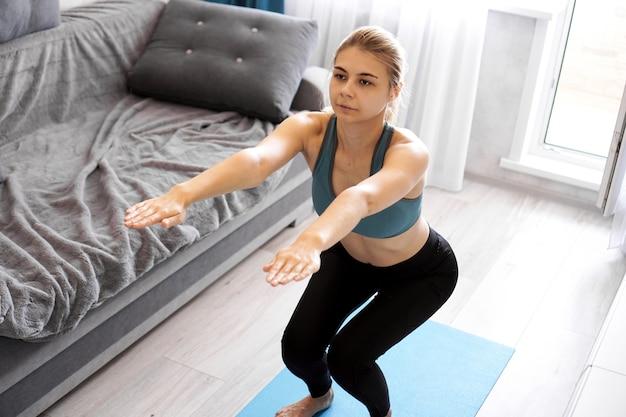 Mulher se exercitando e fazendo agachamento em casa