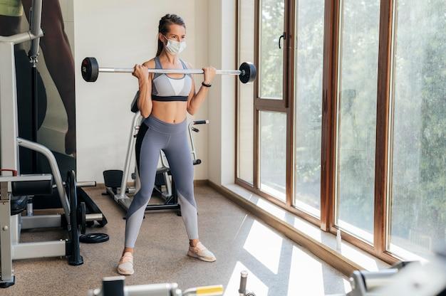 Mulher se exercitando na academia com equipamento e máscara