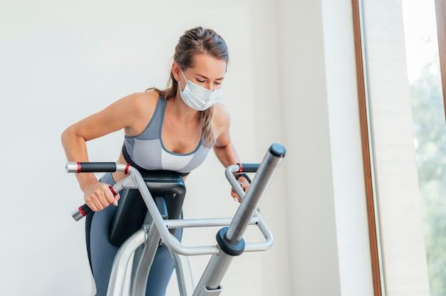 Mulher se exercitando na academia com máscara e equipamento