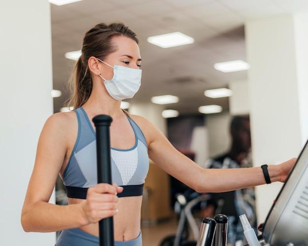 Mulher se exercitando na academia com máscara