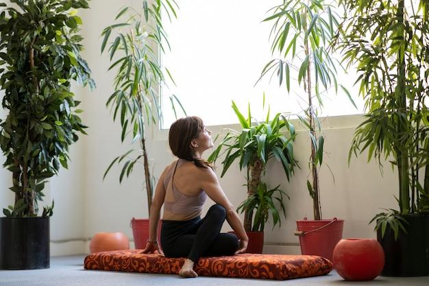 Mulher se flexiona, sentada em um tapete, olhando para a janela com plantas ou plantas ao redor