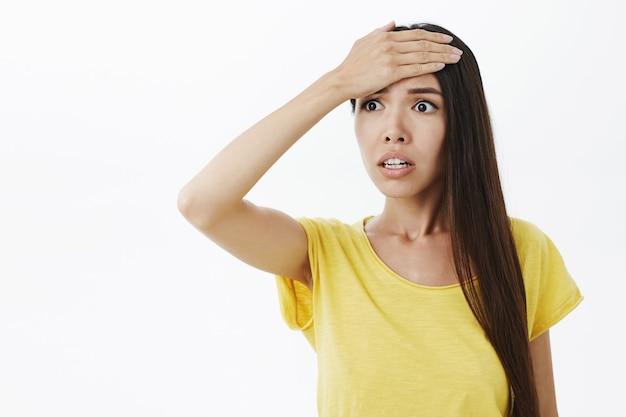 Mulher se lembrou de uma coisa importante que ela esqueceu de fazer sentindo-se ansiosa e preocupada socando a testa com a palma da mão olhando para a esquerda preocupada