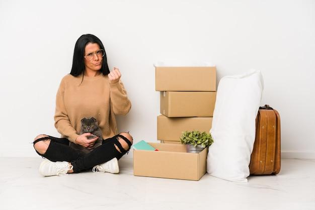 Mulher se mudando para casa, isolada no fundo branco, mostrando o punho para a câmera, expressão facial agressiva.