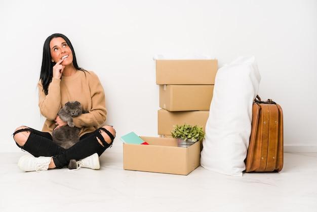 Mulher se mudando para casa isolada no fundo branco relaxado pensando em algo olhando para um espaço de cópia.