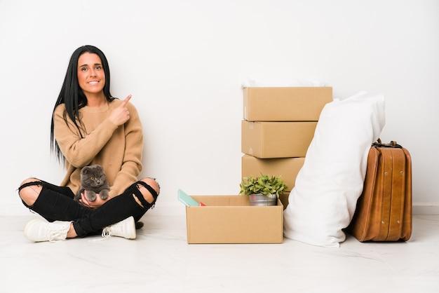 Mulher se mudando para casa, isolada no fundo branco, sorrindo e apontando de lado, mostrando algo no espaço em branco.