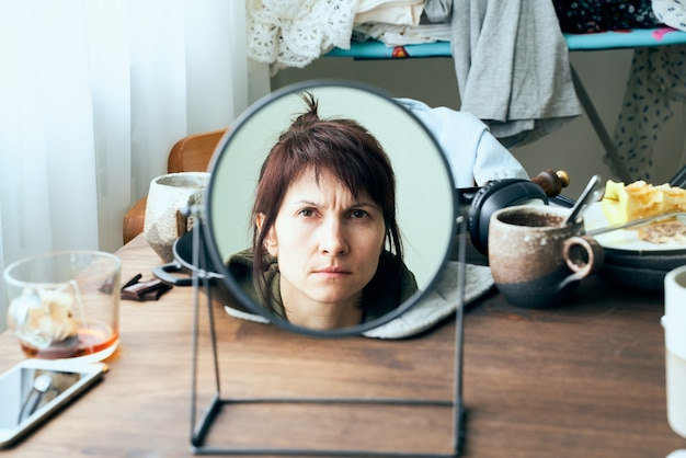Mulher se olha no espelho contra bagunça, pratos sujos, pilhas de roupas