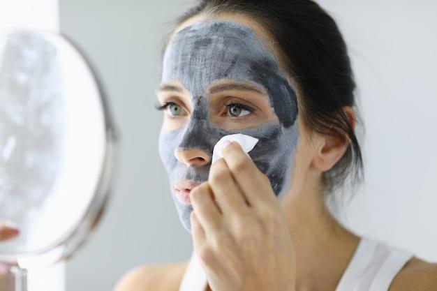Mulher se olha no espelho e enxágue a máscara cosmética.