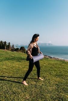 Mulher se prepara para colocar seu tapete de ioga na grama em frente ao mar. copie o espaço