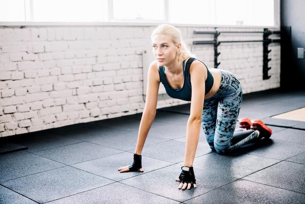 Mulher se preparando para fazer exercícios no chão
