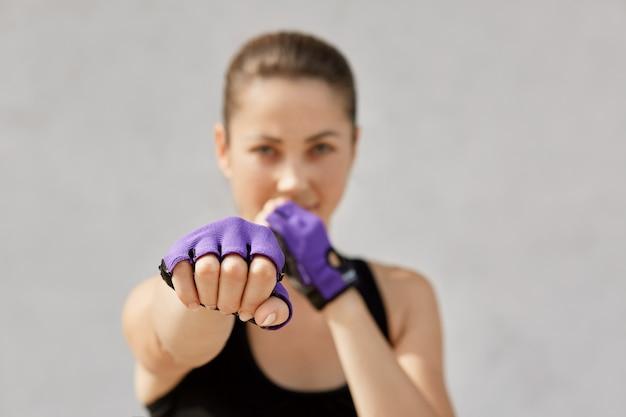Mulher se preparando para o treino no estúdio de esporte. fêmea em luvas de sportswear e fitness em pé isolado na cinza