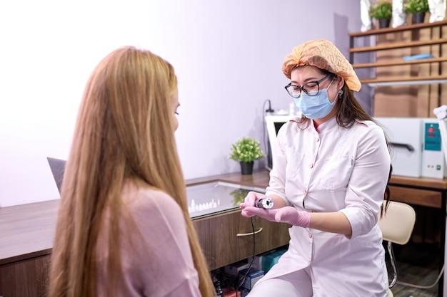 Mulher se preparando para receber tratamento para a pele do cabelo em uma sala iluminada de cosmetologia, obter informações sobre equipamentos